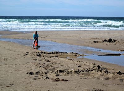 photo of a child building a dam on Rockaway Beach, Oregon by Nancy Zavada