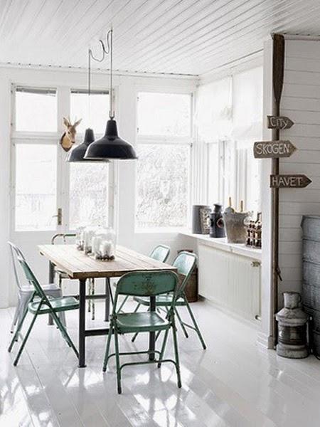 Wiszące czarne lampy nad drewnianym stołem z lśniąco białą podłogą