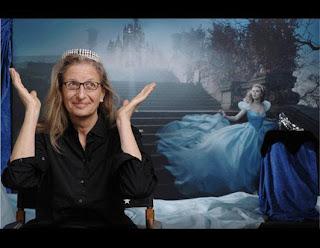 "Image: Annie Leibovitz, a 61-year-old, bespecled woman with a prominent nose, sits in a directors chair wearing a 62-carat, diamond tiara. Her palms are pointed to the heavens, as if to say ""all done!&quote; To her left, on a draped pedestal, there is a high-heeled, glass slipper. Behind them both, Actress Scarlett Johansen runs hurriedly down an old-style garden staircase; looking around for her carriage to escape from the Disney World castle. She wears the same tiara and her ball gown flows behind her, up the steps. On the landing behind her, the same glass slipper can be seen, highlighted by a spotlight. Caption:"