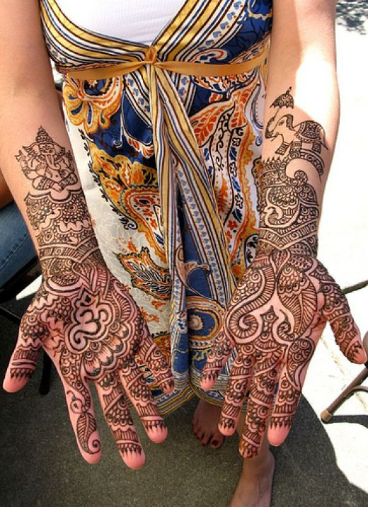 Elephant drawn in left palm and Lord Ganesh painted on a girls right palm with Mehandi.