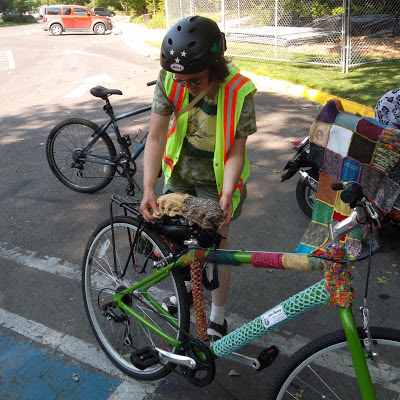 Cynthia Parkhill places knit-swatch seat cover on yarn-bombed bicycle