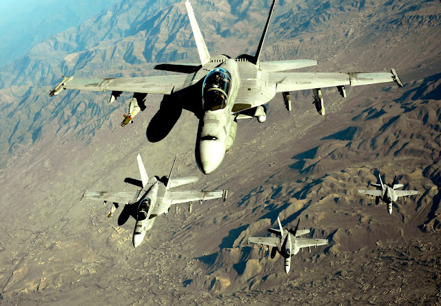 Four U.S. Navy F/A-18 Hornets approach a KC-10 Extender for refueling