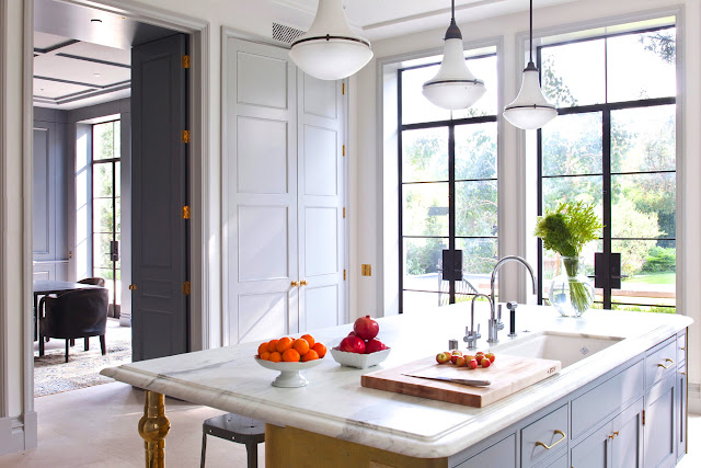 kitchen designed by William Hefner with panel doors, white cabinets and a yellow island with a marble countertop