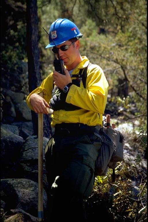 Wildland firefighter communicating with a radio