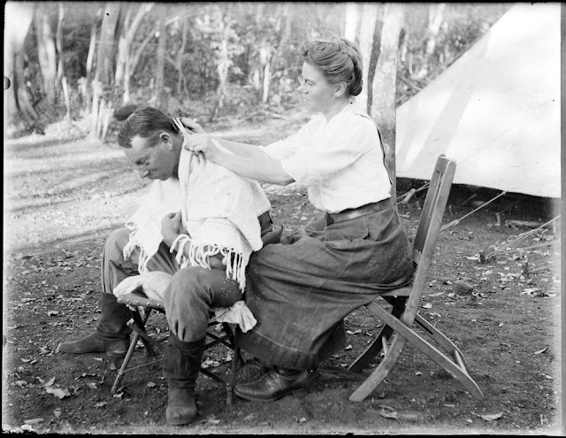 Mrs Charlotte Teale trims Edmund Teale's hair. Geological field camp, Portuguese East Africa. 1911. E.O. Teale photograph collection.