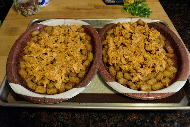 A picture of the two football plates, on a baking sheet, with the tater tots and chicken mixture.