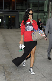 Rihanna with headphones and sunglasses at Heathrow Airport