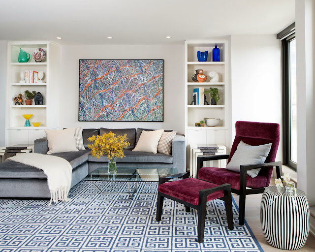 Modern living room with graphic blue Greek key rug, silver blue velvet sectional sofa, glass coffee table and burgundy accent chair and ottoman