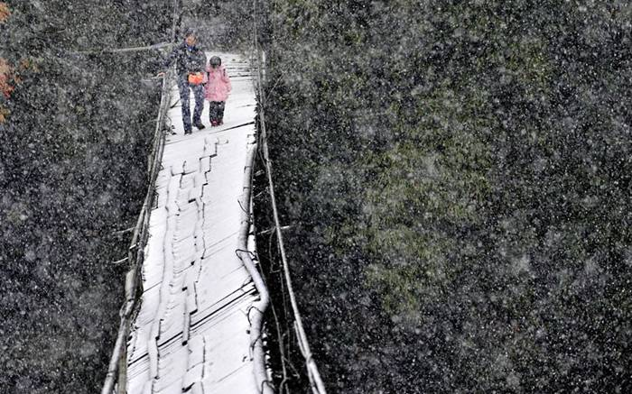 Zhao Jihong and her four-year-old daughter Zi Yi cross a broken bridge in the snow to get to school in Dujiangyan, Sichuan Province, China. Shawan village's only connection to the outside is a wooden bridge. However, this bridge was damaged by flooding, leaving it extremely precarious and leaning dangerously to one side.Picture: Quirky China News / Rex Features