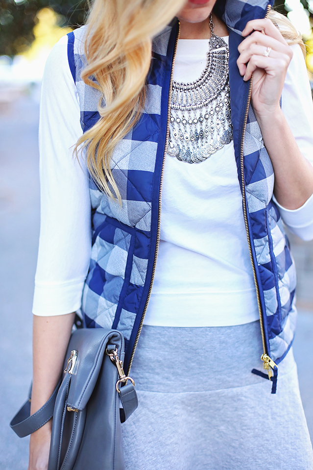 blue and gray plaid vest with silver coin necklace
