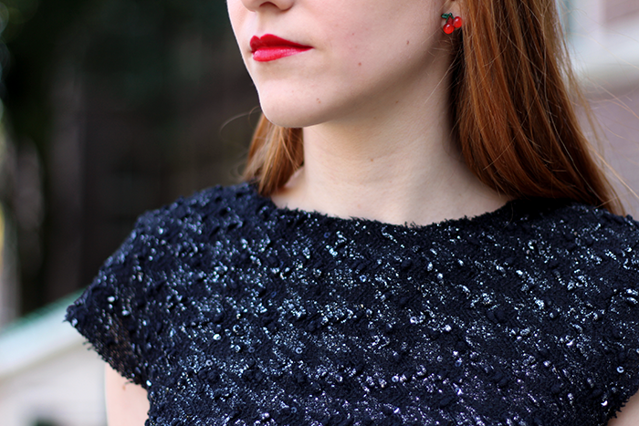 Blogger outfit detail with tweed houndstooth top, red lipstick and cherry earrings