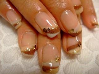 Estas elegantes uñas están realizadas en colores café y dorados, en un french sencillo, con base en color piel, en el cual se realizan líneas curvas de los