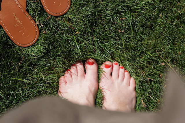 pedicure foot in grass sandals painted toenails summer