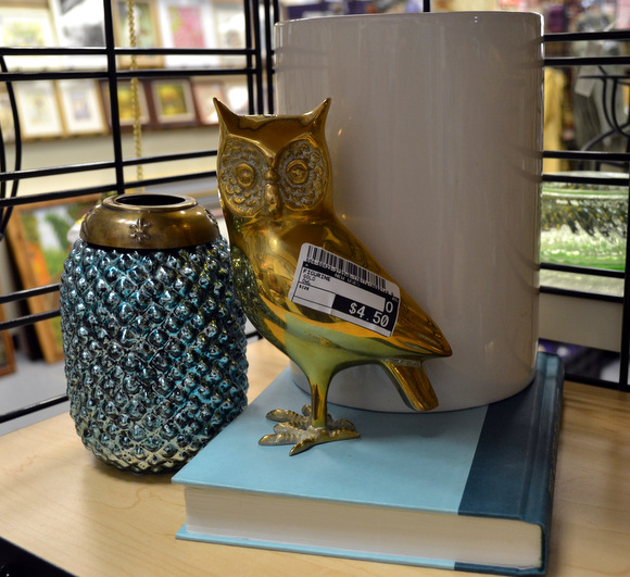 Brass owl on book with white vase