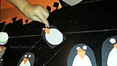 gluing eyes on penguin crafts