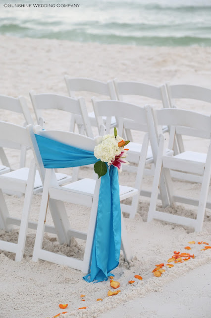 a unique design for your aisle way by tying a sash to the side and attaching a fresh flower arrangement