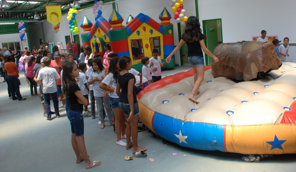 Crianças se divertem nos brinquedos montados pela Prefeitura após a inauguração do novo prédio escolar em Bonsucesso