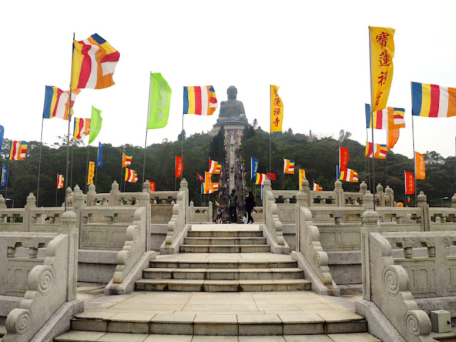 View of the Big Buddha / Tian Tan Buddha with colourful flags across the podium in Ngong Ping Piazza, Lantau Island, Hong Kong