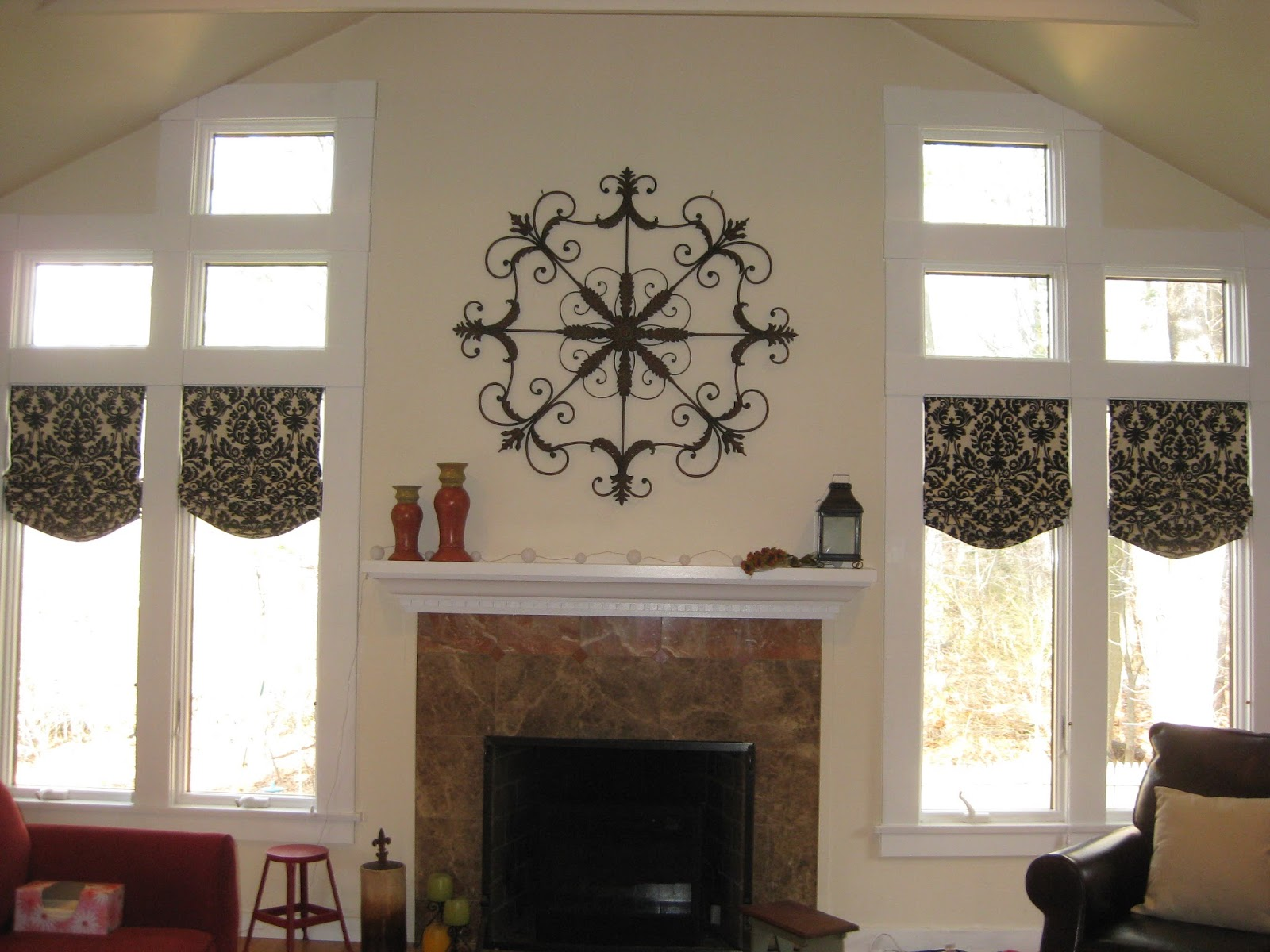 once installed these functional shades the iron medallion display above the fireplace beautifully relaxed roman