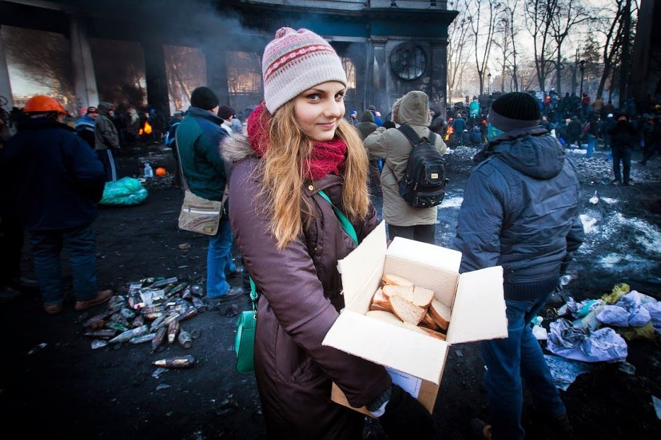 35 moments of violence that brought out incredible human compassion - a girl delivers sandwiches to protesters amongst the chaos