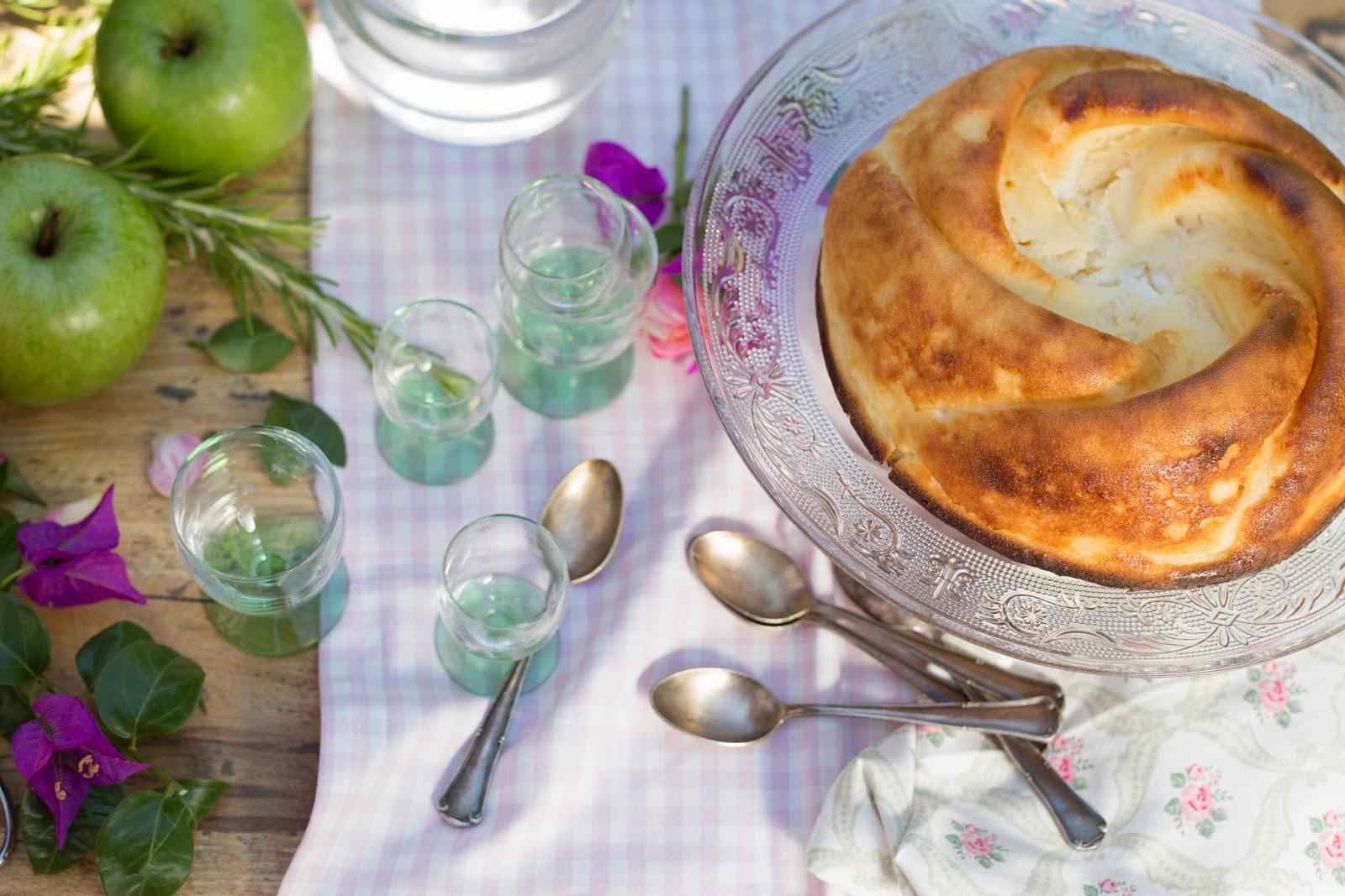 Tarta de requesón en cake stand de cristal con cucharillas de plata antiguas y cristalería con pie de cristal verde. Manzanas verdes y flores purpuras.