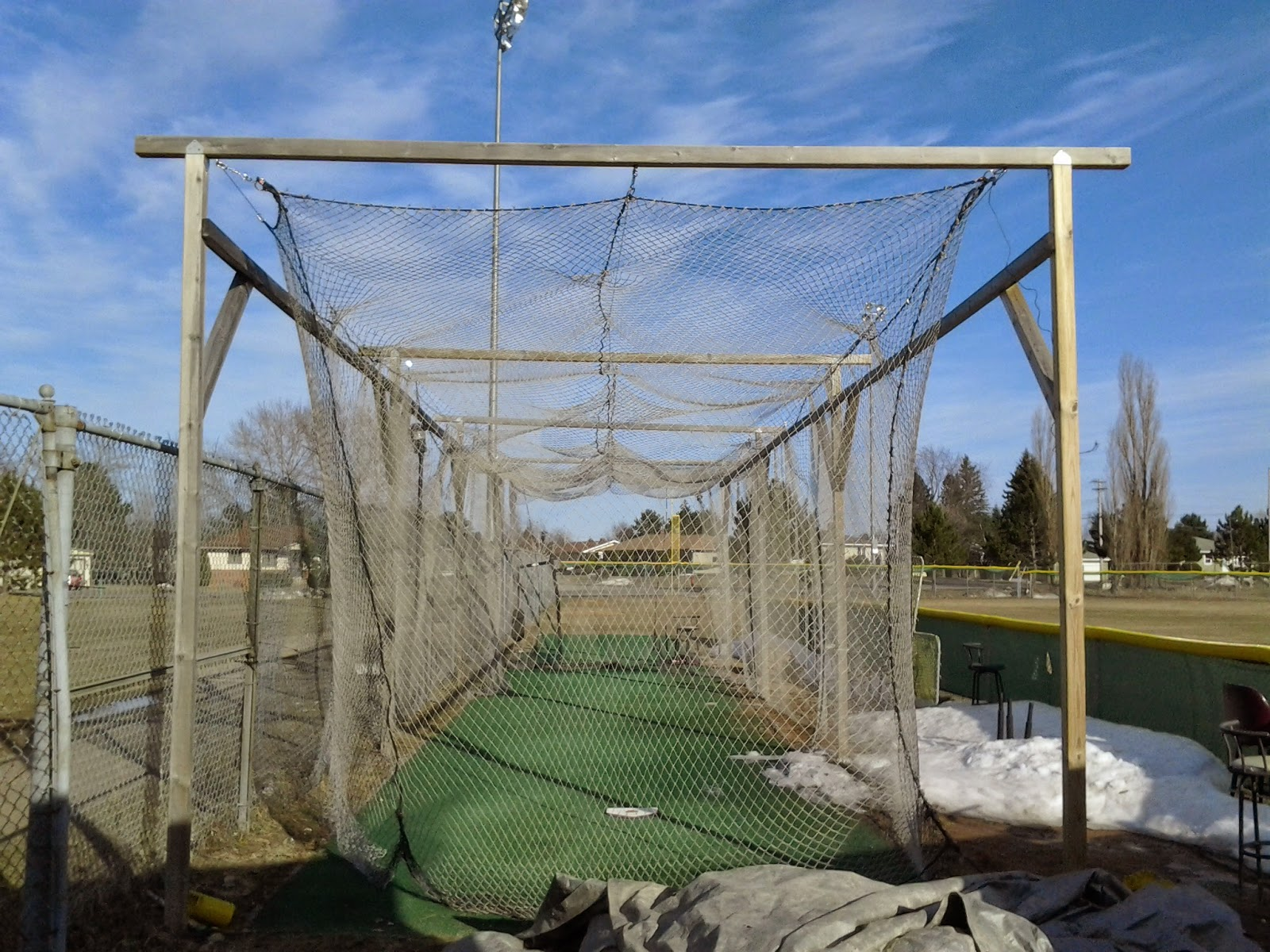 Ely High school field batting cage, 2014, spring, snow on the side