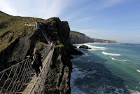 Tourists make their way across Carrick-a-Rede Rope Bridge on the Causeway coast, north of Belfast April 8, 2015. (Credit: Reuters/Cathal McNaughton) Click to Enlarge.