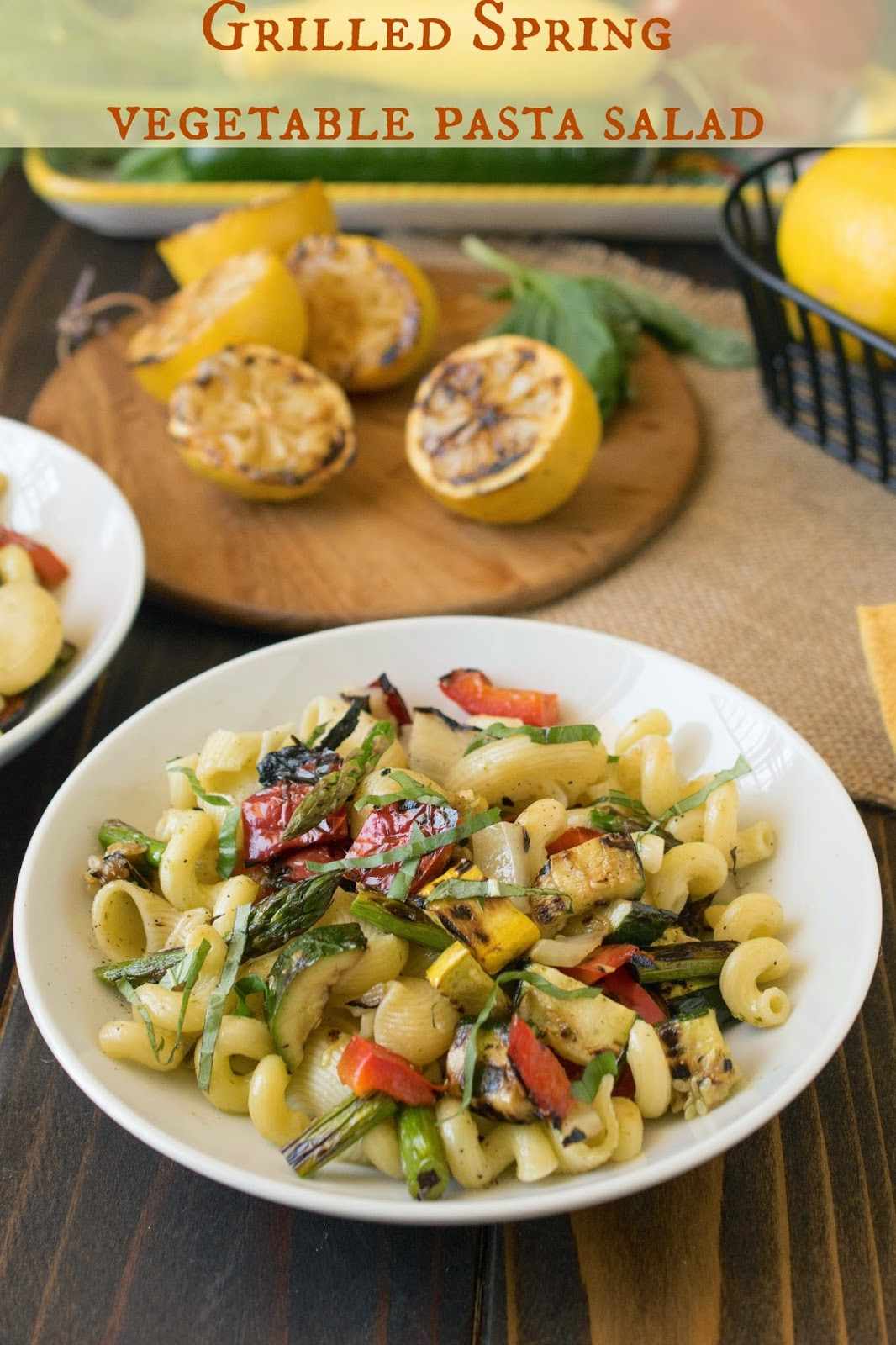 Grilled Spring vegetable pasta salad in a white bowl with grilled lemon halves on a board behind