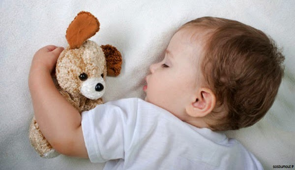 Bébé mimi qui dort avec doudou