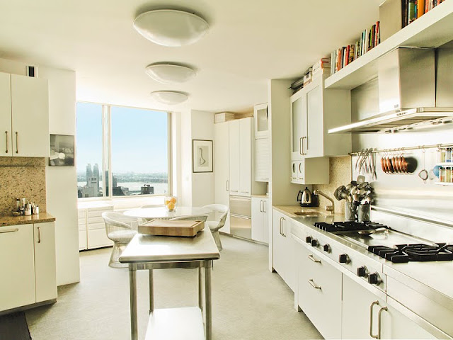 open kitchen with white cabinets and granite counter tops, and metal island. The hood is very flat and goes straight up into a floating bookshelf