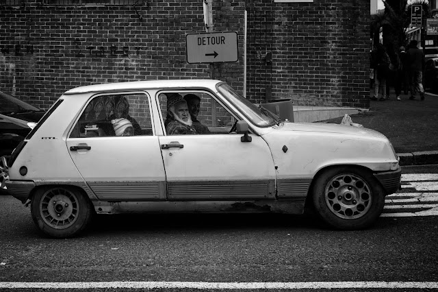 A family sits in their ancient Renault car beneath a sign reading Detour.