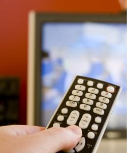 main qui tient une télécommande dirigée sur un téléviseur