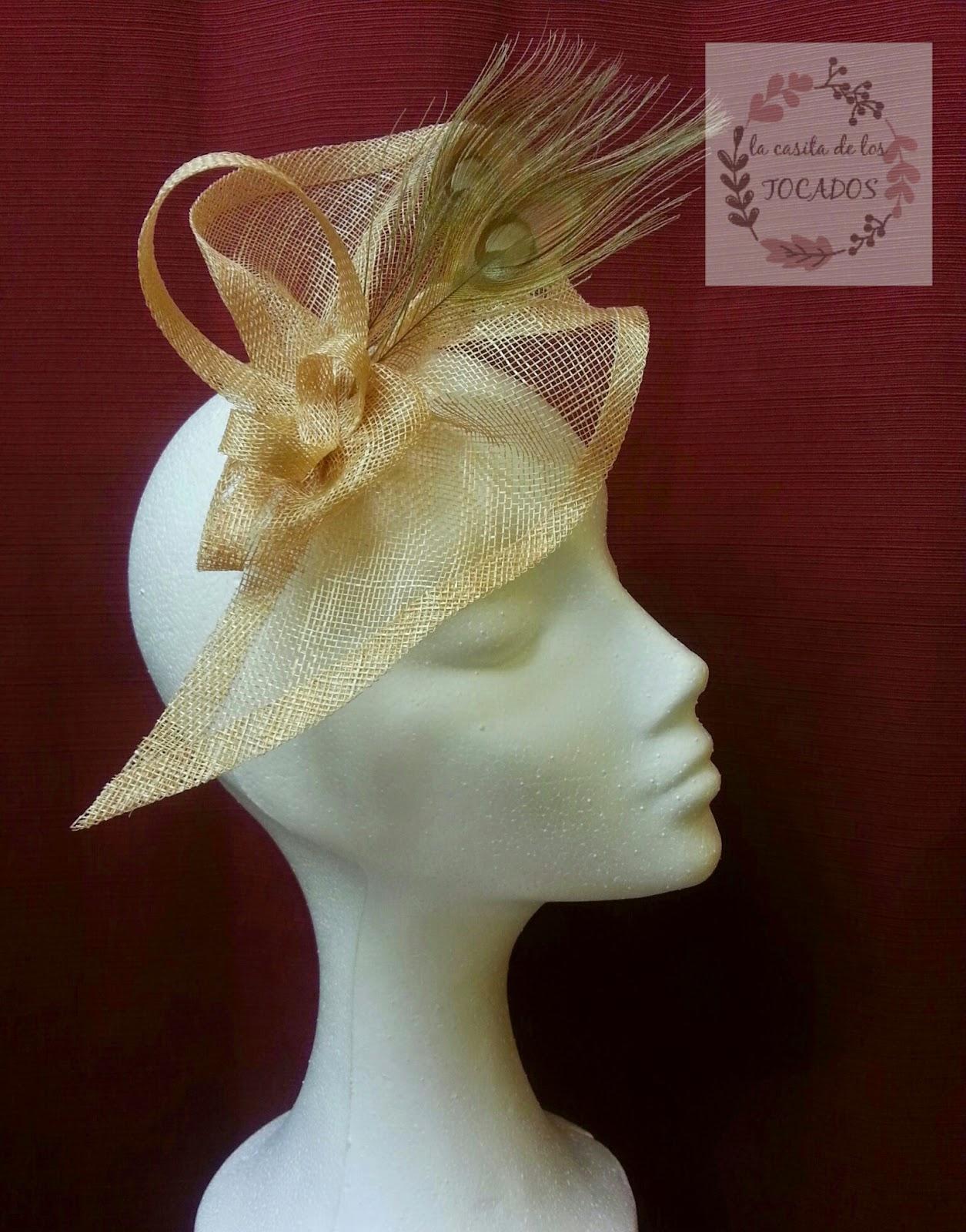 tocado original para boda con forma a pico en color dorado con dos plumas de pavo real también en dorado