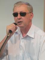 Foto alinhada à esquerda: Segurando o microfone, Ricardo Sewaald - Presidente do Conselho Municipal dos Direitos e Cidadania das Pessoas com Deficiência
