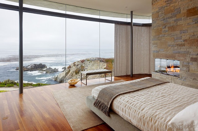 Picture of the king size bed by the fireplace looking out to the ocean through the glass wall