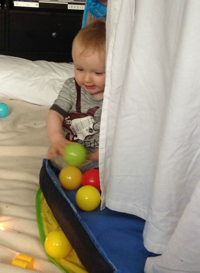 baby playing with coloured balls inside a den made with a sheet