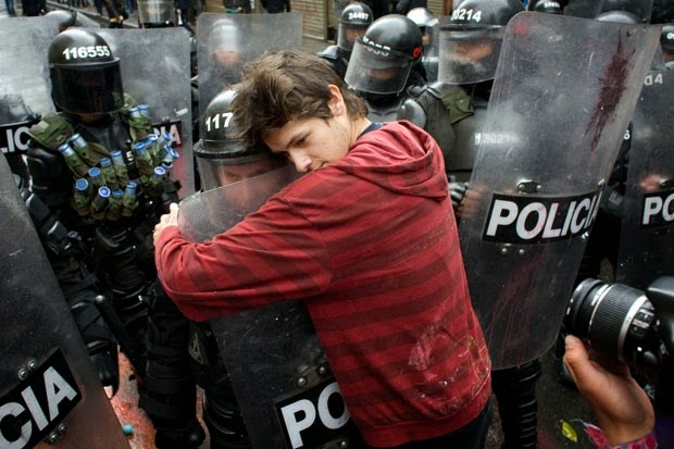 35 moments of violence that brought out incredible human compassion - a student protesting education reform hugs a policeman