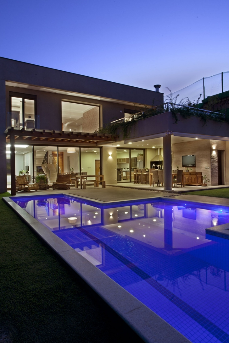 Swimming pool at night in Elegant dream home in Sao Paulo by Pupo Gaspar Arquitetura