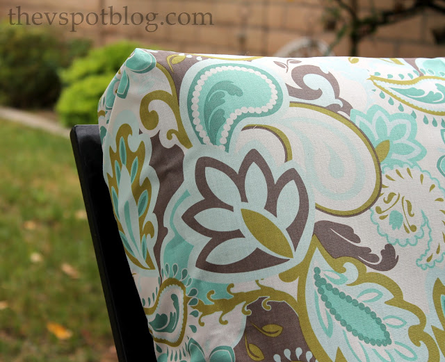 Cushion with teal and brown paisley-like fabric