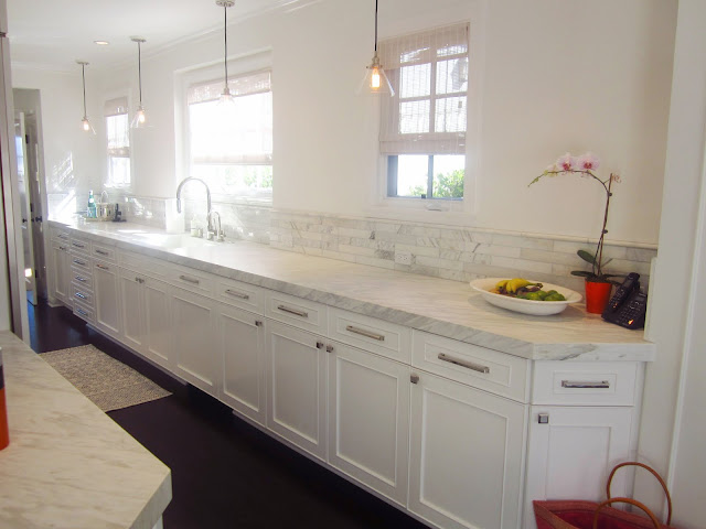 galley kitchen with marble counters, white cabinets with polished nickle drawer pulls, pendent lights, and dark wood floors