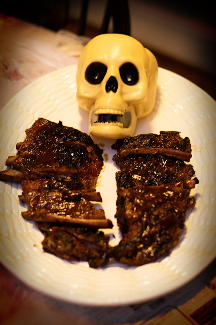 A skull head with BBQ ribs on a platter.