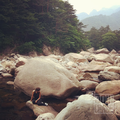 A girl posing by large rocks in a river at Seoraksan National Park in South Korea.