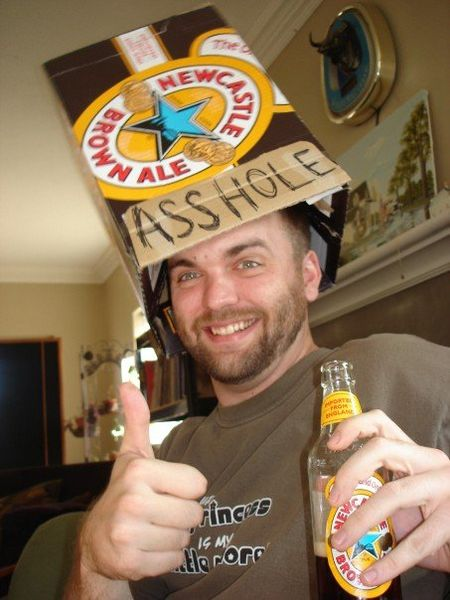 a drunk man drinking a beer and wearing a hat made from an empty cardboard beer case with the word asshole written on it