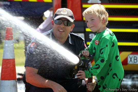L-R: Station officer Hayden Palmer, Ricky Walsh, 5, Hastings, taking his turn on the hose, at Harold's Fun Day and Picnic At The Park, run by Hawkes Bay Life Education Trust, at Hawke's Bay Regional Sports Park, Hastings. photograph