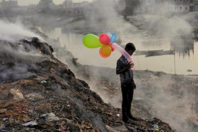 صبي يلعب مع البالونات على شاطئ نهر بوريجانجا، بنجلاديش تصوير |أندرو بيراج