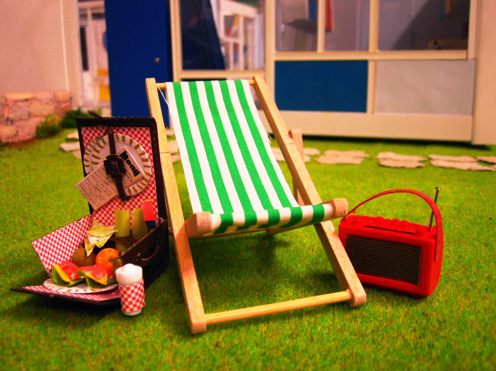 Miniature deck chair, radio and filled picnic hamper on the lawns in front of a miniature Rose Seidler house.