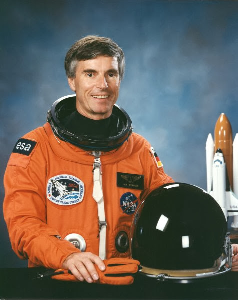 Official portrait of STS-42 Payload Specialist Ulf Merbold wearing a launch and entry suit (LES) with space shuttle orbiter model displayed in the background. Merbold is representing ESA during the International Microgravity Laboratory 1 (IML-1) mission aboard Discovery, Orbiter Vehicle (OV) 103. Credit: NASA