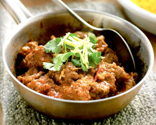Spicy Pork Curry: Shoulder of pork in a spicy gravy base garnished with coriander in the pan it was prepared in