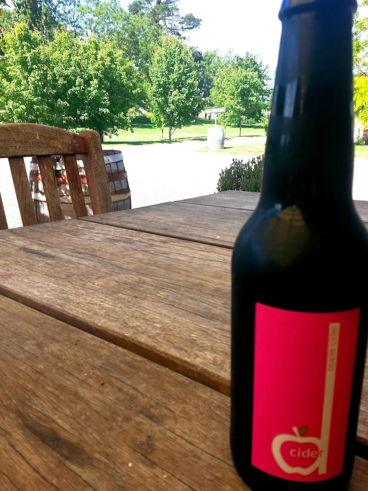 Bottle of Dcider on a patio table  in a garden.