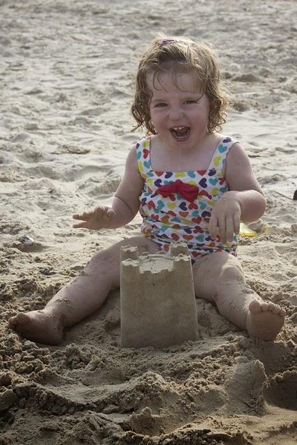 anak perempuan main pasir di pantai